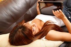 Usando un Tablet PC en el sofá Fotos de archivo