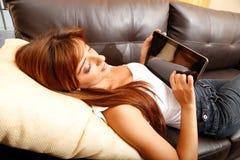 Usando un Tablet PC en el sofá Foto de archivo libre de regalías