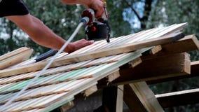 Usando una máquina a clavar en las tejas de tejado de madera de la tabla del cedro metrajes
