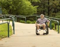 Usando una rampa de acceso concreta de la silla de ruedas Foto de archivo