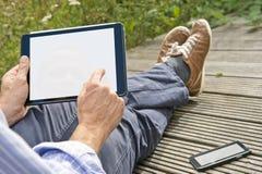 Usando una tableta afuera Imagen de archivo libre de regalías
