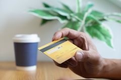 Usando una tarjeta de crédito a pagar en línea, utilice un smartphone para las compras en línea, una mano masculina sostiene una  fotos de archivo libres de regalías