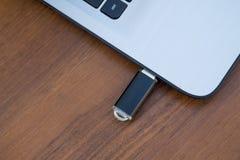 USB记忆棍子或闪光驱动附有膝上型计算机的边 库存照片