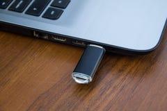 USB记忆棍子或闪光驱动附有膝上型计算机的边 免版税库存图片
