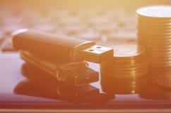 USB说谎在黑膝上型计算机身体的存储卡和一些枚硬币在他的键盘前面的 与USB outp的虚拟内存存贮 免版税库存图片