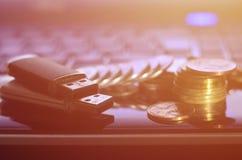 USB说谎在黑膝上型计算机身体的存储卡和一些枚硬币在他的键盘前面的 与USB outp的虚拟内存存贮 图库摄影
