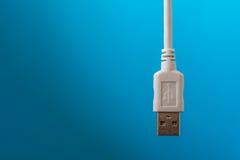 USB连接缆绳在白色安置了在蓝色背景 图库摄影