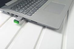 Usb闪光驱动被插入入在一张白色木书桌上的膝上型计算机插口 现代技术 免版税库存照片