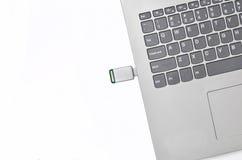 USB闪光驱动被插入入在白色背景的一台膝上型计算机 现代数字式媒介 免版税库存照片