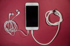 有usb缆绳和耳机的一个电话 免版税库存照片