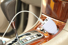 USB adapter converter plug. With charging cable on a car Royalty Free Stock Photo