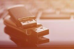 USB bildkort som ligger på den svarta bärbara datorn, case framme av hans tangentbord Lagring för faktiskt minne med USB outpuen Fotografering för Bildbyråer