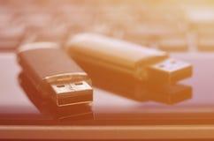 USB bildkort som ligger på den svarta bärbara datorn, case framme av hans tangentbord Lagring för faktiskt minne med USB outpuen Royaltyfri Bild