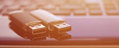 USB bildkort som ligger på den svarta bärbara datorn, case framme av hans tangentbord Lagring för faktiskt minne med USB outpuen Royaltyfri Foto