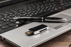 USB-Blitz-Antrieb, der auf Computerlaptoptastatur und -stift liegt Lizenzfreie Stockfotografie