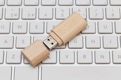 USB-Blitz-Antrieb hölzern auf weißer Tastatur Stockfotografie