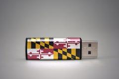Usb-Blitz-Antrieb mit der Maryland-Staatsflagge auf grauem Hintergrund Stockbilder