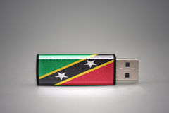 Usb-Blitz-Antrieb mit der Staatsflagge des Heiligen Kitts und Nevis auf grauem Hintergrund Lizenzfreie Stockfotografie