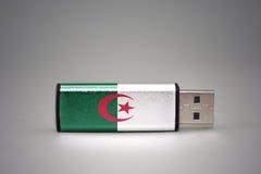 Usb-Blitz-Antrieb mit der Staatsflagge von Algerien auf grauem Hintergrund Lizenzfreies Stockfoto