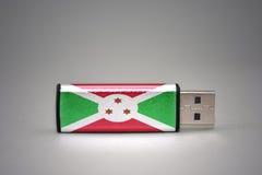 Usb-Blitz-Antrieb mit der Staatsflagge von Burundi auf grauem Hintergrund Stockfotos