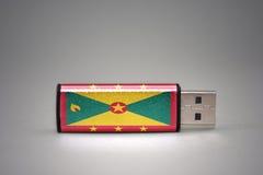 Usb-Blitz-Antrieb mit der Staatsflagge von Grenada auf grauem Hintergrund Stockfotografie