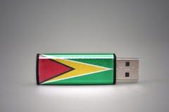 Usb-Blitz-Antrieb mit der Staatsflagge von Guyana auf grauem Hintergrund Stockfotos