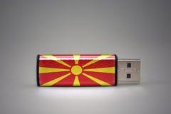 Usb-Blitz-Antrieb mit der Staatsflagge von Macedonia auf grauem Hintergrund Stockfotos