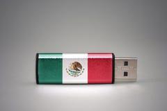 Usb-Blitz-Antrieb mit der Staatsflagge von Mexiko auf grauem Hintergrund Stockbild