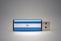 Usb-Blitz-Antrieb mit der Staatsflagge von Nicaragua auf grauem Hintergrund Lizenzfreie Stockfotografie