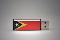 Usb-Blitz-Antrieb mit der Staatsflagge von Osttimor auf grauem Hintergrund Stockfotos