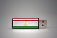 Usb-Blitz-Antrieb mit der Staatsflagge von Tadschikistan auf grauem Hintergrund Stockfotografie