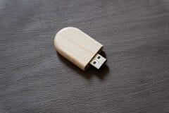 Usb-Blitz-Antrieb mit Holzoberfläche auf Schreibtisch für USB-Port-Einsteckcomputerlaptop für Überweisungsdaten und Aushilfsgesch Stockbild