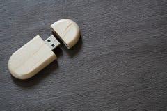 Usb-Blitz-Antrieb mit Holzoberfläche auf Schreibtisch für USB-Port-Einsteckcomputerlaptop für Überweisungsdaten und Aushilfsgesch Stockfotos
