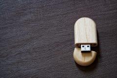 Usb-Blitz-Antrieb mit Holzoberfläche auf Schreibtisch für USB-Port-Einsteckcomputerlaptop für Überweisungsdaten und Aushilfsgesch Lizenzfreie Stockfotos