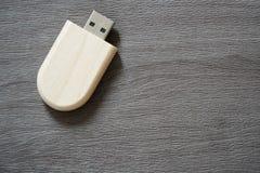 Usb-Blitz-Antrieb mit Holzoberfläche auf Schreibtisch für USB-Port-Einsteckcomputerlaptop für Überweisungsdaten und Aushilfsgesch Lizenzfreie Stockfotografie