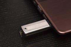 USB-de aandrijving van de metaalflits verbond met de hand met laptop stock foto's