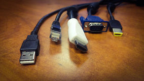 USB, Ethernet, HDMI, VGA, display port cables on wood table Royalty Free Stock Photos