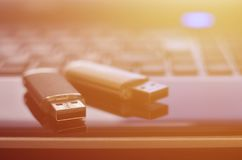 USB flash cards lying on black laptop case in front of his keyboard. Virtual memory storage with USB outpu. T royalty free stock photo