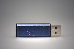 Usb flash drive with the alaska state flag on gray background. Royalty Free Stock Photography