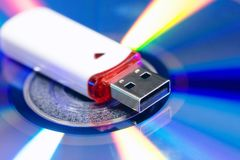 Usb flash drive on cd disc background. new and old technology. equipment to store information. colored blue pink green and yellow royalty free stock photography
