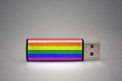 Usb flash drive with the gay rainbow flag of on gray background. Stock Photography