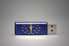 Usb flash drive with the indiana state flag on gray background. royalty free stock photo