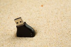 Usb flash drive lost in the sand on the beach.  stock image
