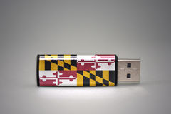 Usb flash drive with the maryland state flag on gray background. stock images
