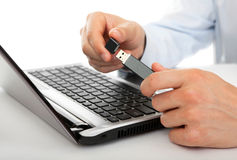 USB flash drive in the men's hands. Against the background of the laptop Royalty Free Stock Image
