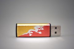 Usb flash drive with the national flag of bhutan on gray background. Stock Images