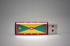 Usb flash drive with the national flag of grenada on gray background. Stock Photography