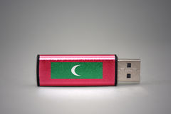 Usb flash drive with the national flag of maldives on gray background. Royalty Free Stock Photo