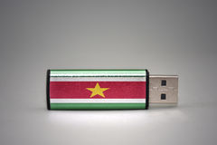 Usb flash drive with the national flag of suriname on gray background. Royalty Free Stock Image