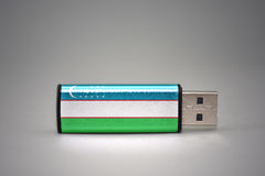 Usb flash drive with the national flag of uzbekistan on gray background. Stock Images